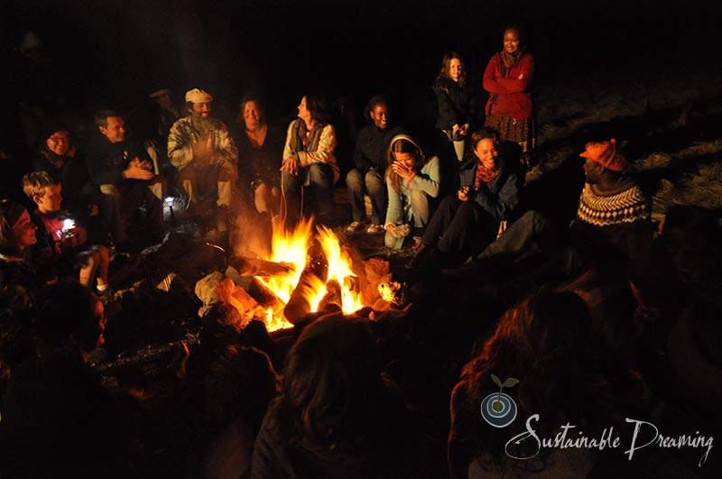 people gathering around an outdoor fire at night